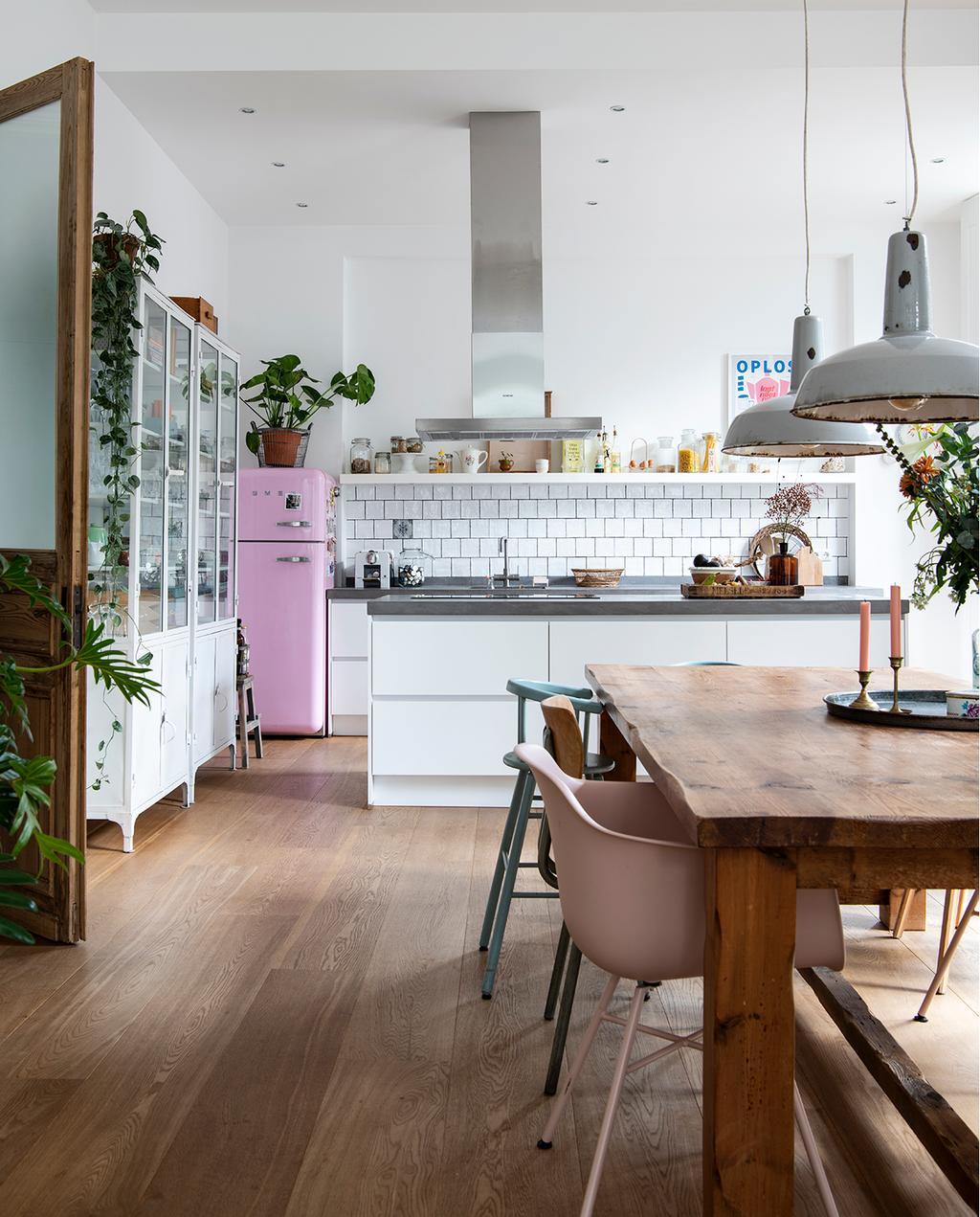 vtwonen 03-2020 | woonkeuken roze koelkast met houten eetkamertafel