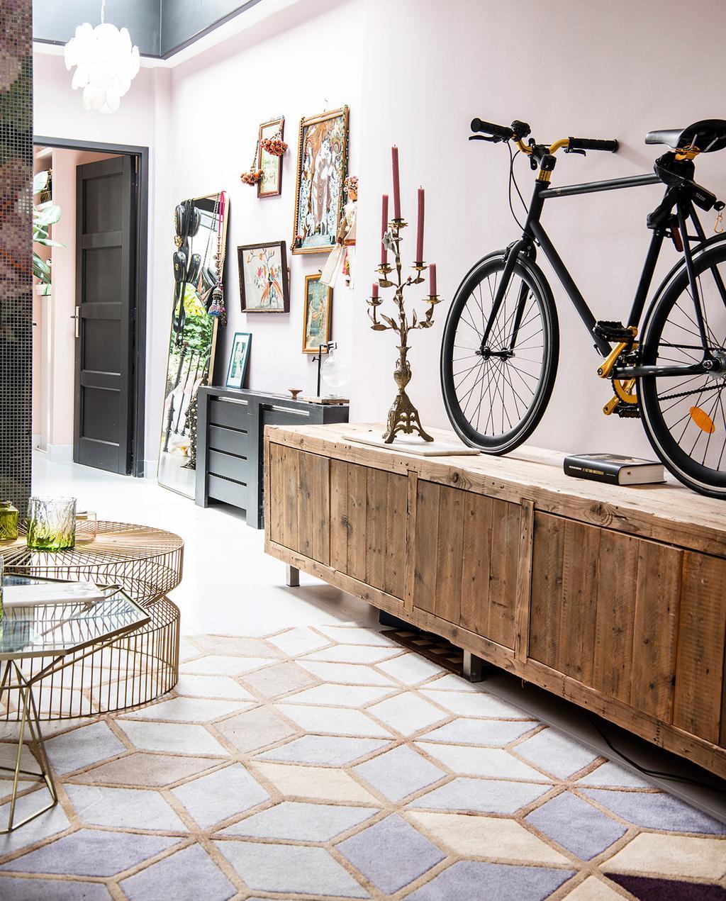 vtwonen 06-2021 | geometrisch vloerkleed met pastelkleuren met een fiets uitgestalt op een lage kast in de Jordaan
