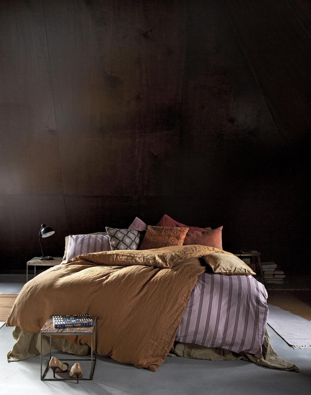 Zacht bed met kussens in prints en zachtgele en roze tinten.