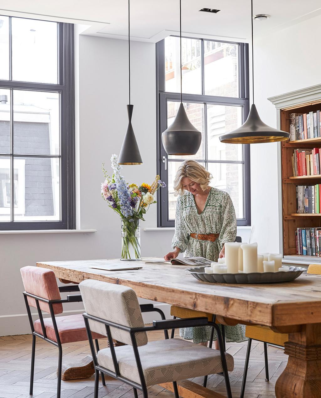 vtwonen 02-2021 | binnenkijken bij Martine eettafel met kaarsen en bloemen, Martine op de achtergrond
