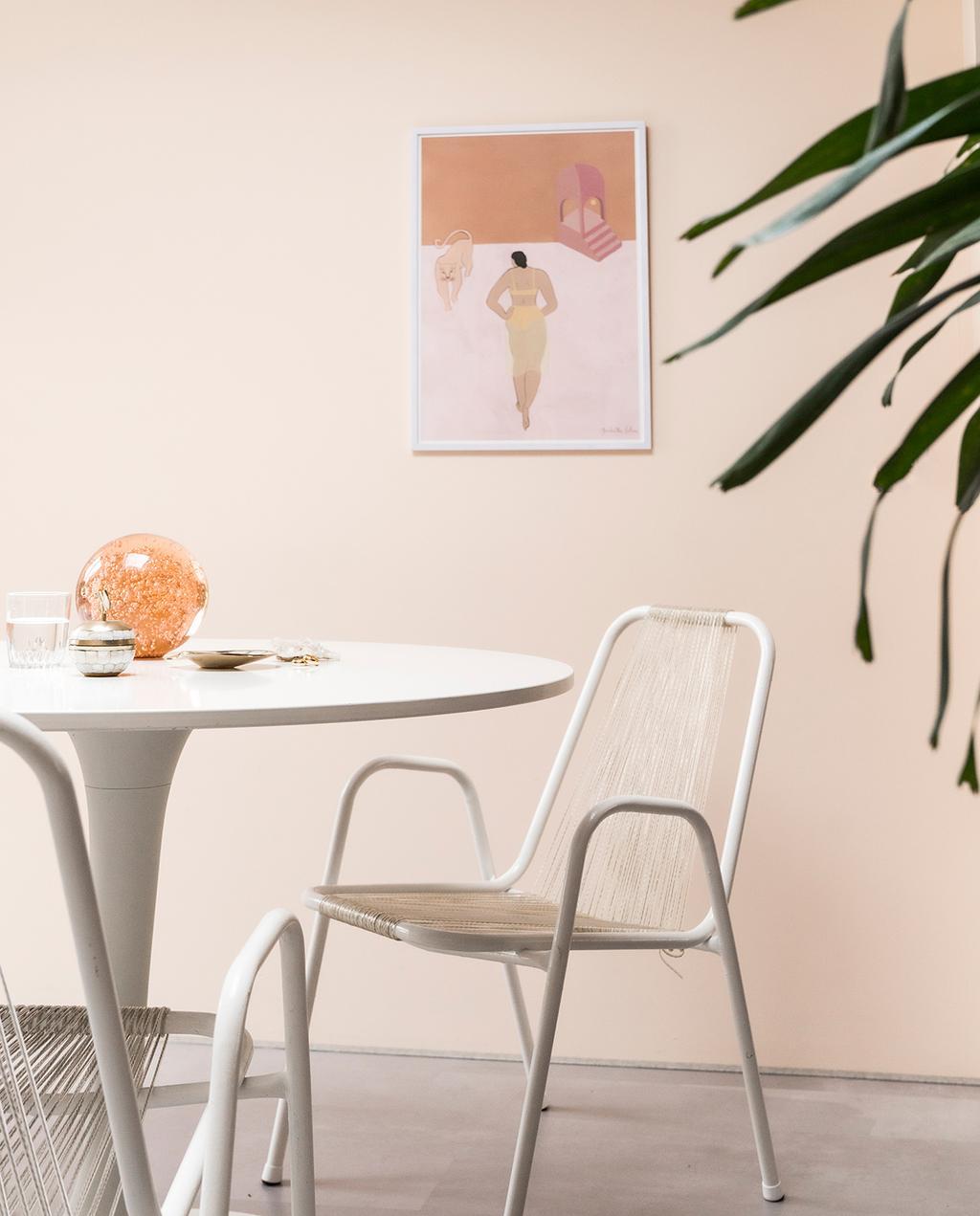 vtwonen special tiny houses 03-2021 | ronde tafel met witte draadstoelen en een poster op de muur