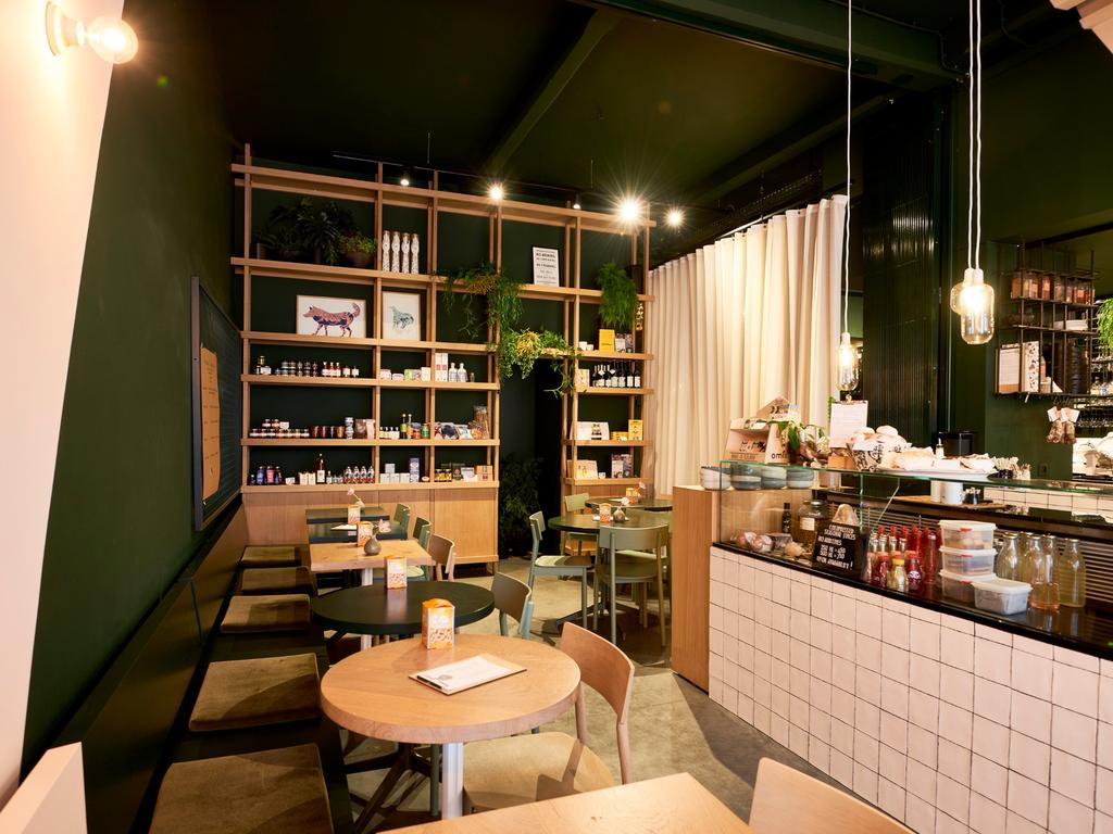 Bar Palmier in Antwerpen met witte tegels en donkergroene muur en jungalow rotan stijl