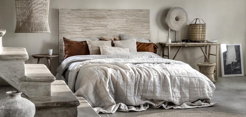 opgemaakt grijs bed dat zicht bevindt in de slaapkamer