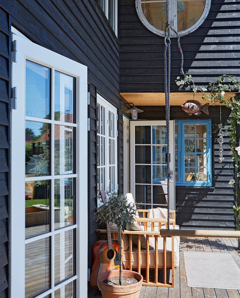 vtwonen special zomerhuizen 07-2021 | tuinbank met gitaar en zwarte latten aan de buitenkant van het huis