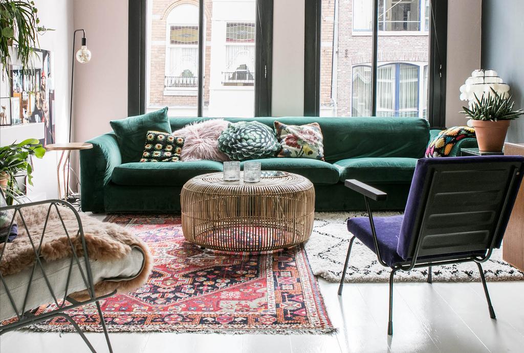 Groene bank met kelim vloerkleden en paarse fauteuil