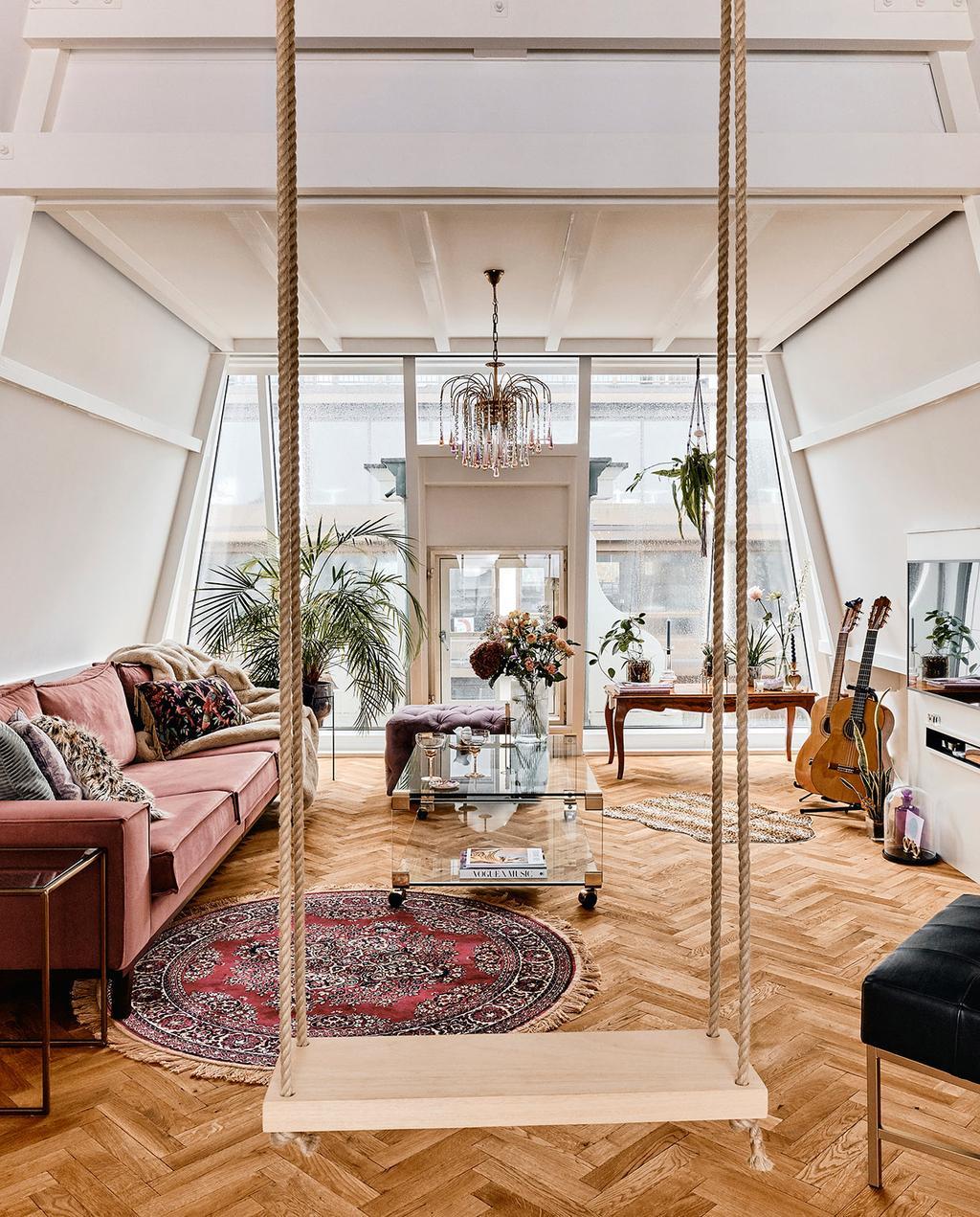 vtwonen 06-2021 | woonkamer van Jessica, met een houten schommel, Perzisch tapijt en een rode bank