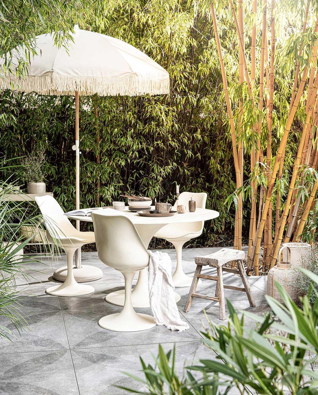 vtwonen 03-2021 | zitplek in tuin met parasol en witte tafel