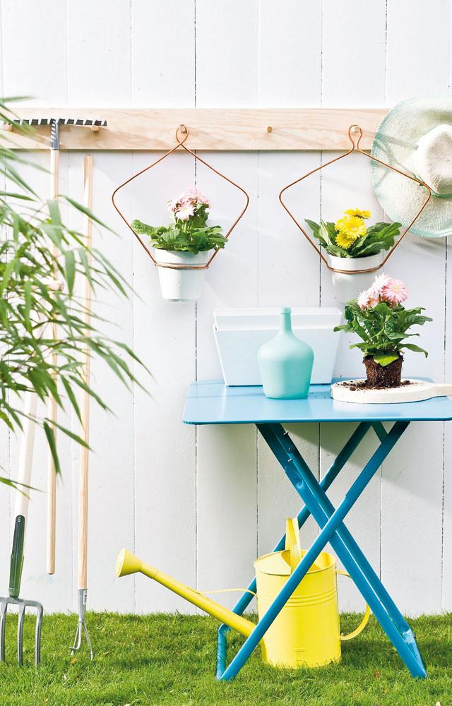 plantenhanger aan de kapstok. Blauwe tuintafel.