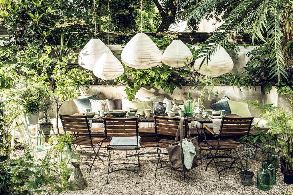 Buitenoase met bistro stoelen en lange tuintafel met lampionnen en weelderig groen