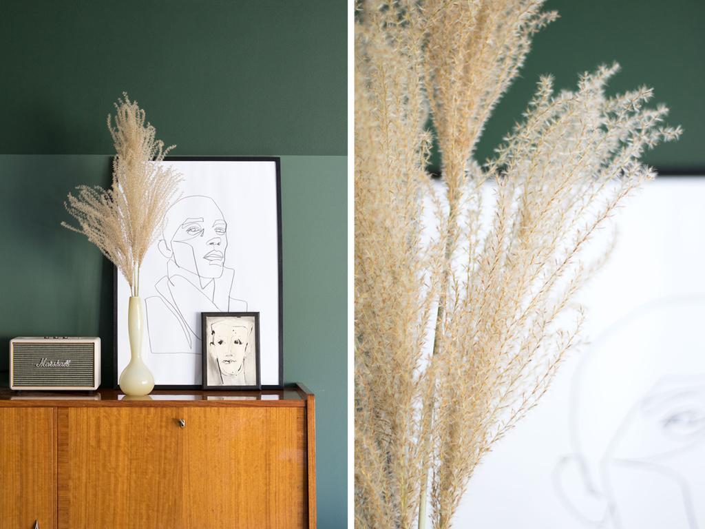 Vintage dressoir met vaasjes met siergras tegen een groene muur bij MY ATTIC thuis