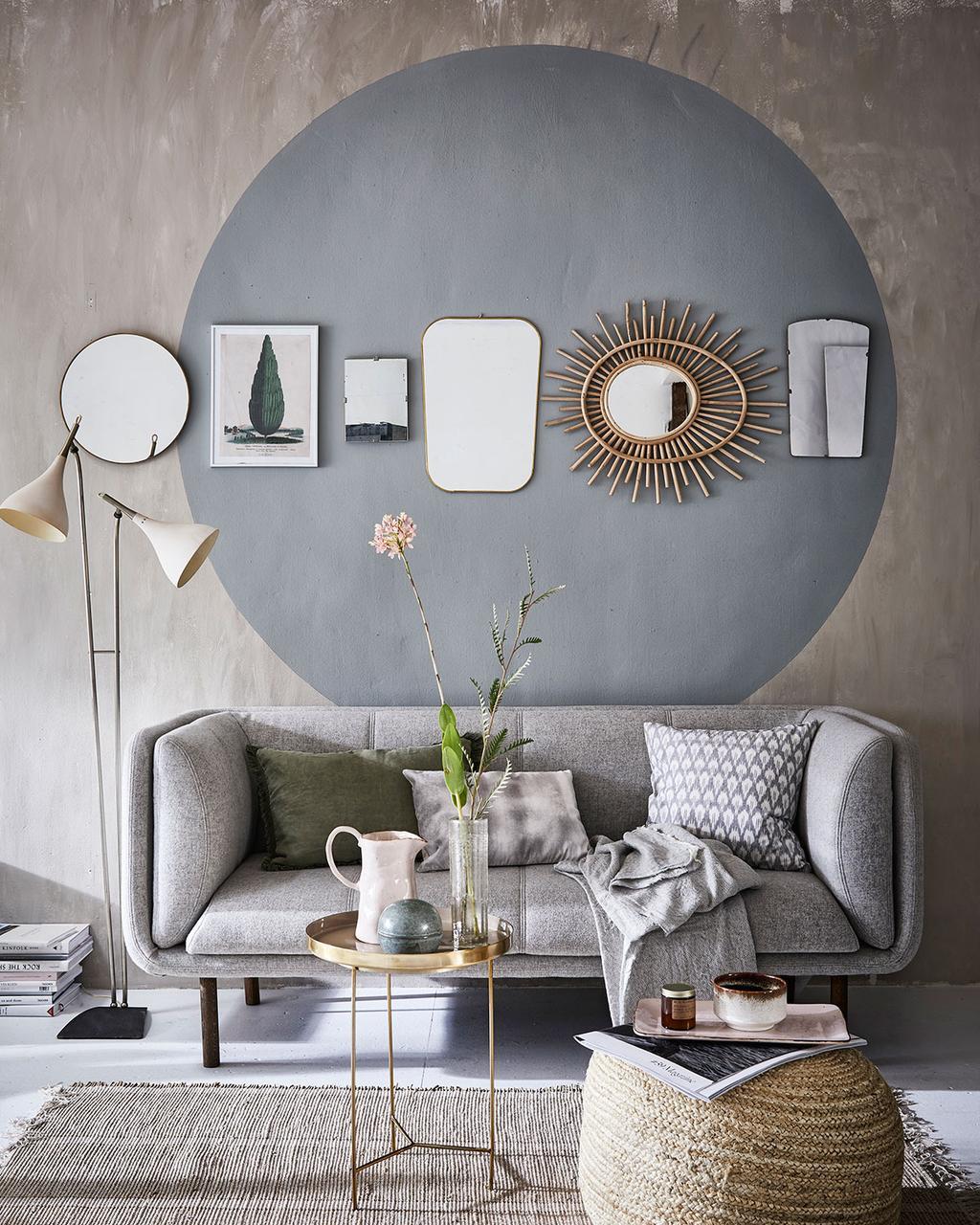 Woonkamer met grijze bank en spiegels in een verfcirkel
