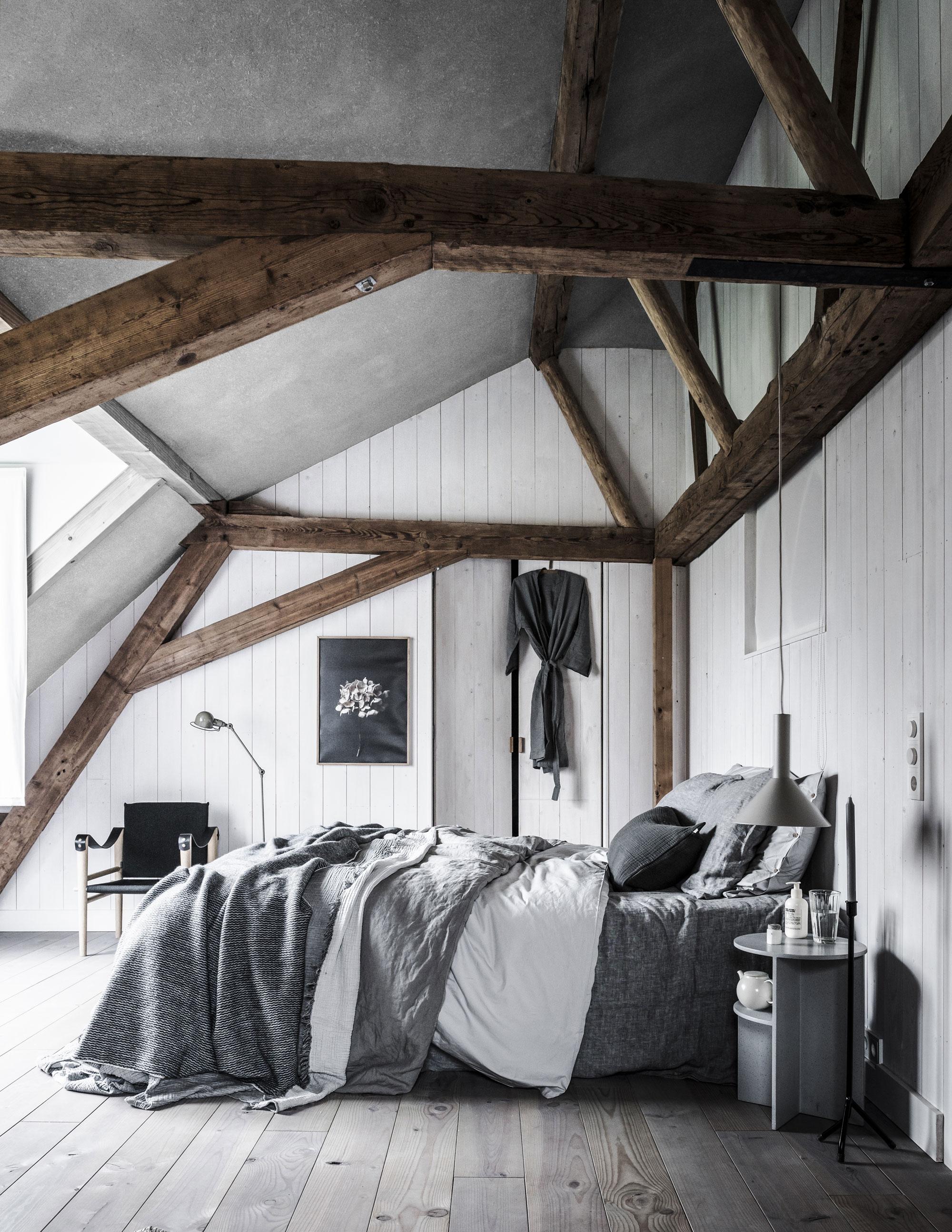 Een grijze slaapkamer met een bed met lakens in verschillende tinten grijs op zolder met houten balken