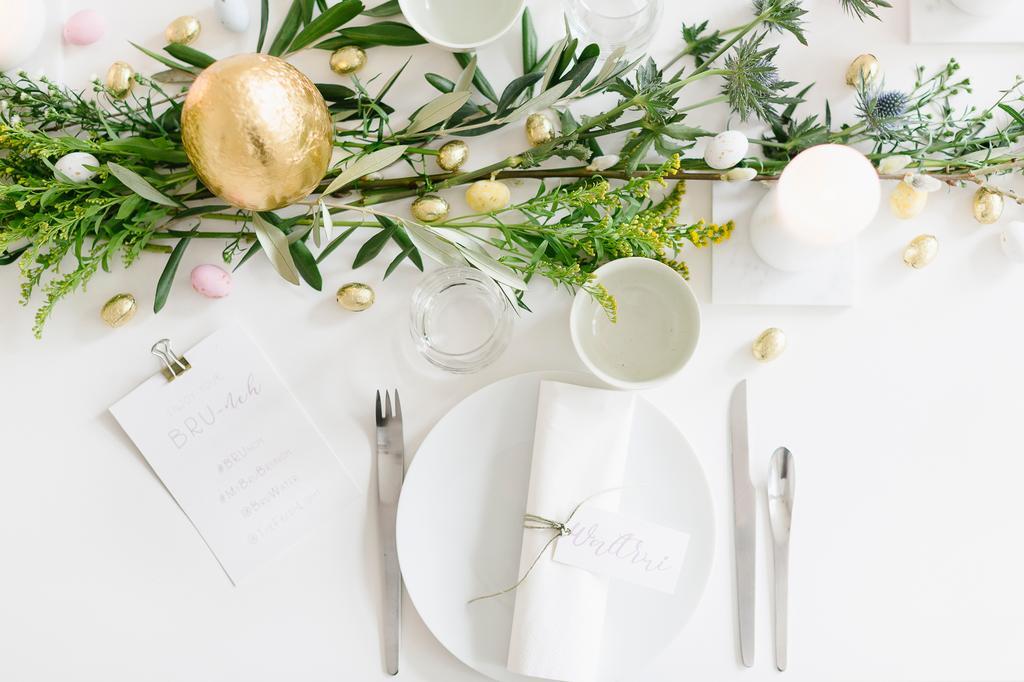witte paastafel van the fresh light met groene takjes en bloemen en servies
