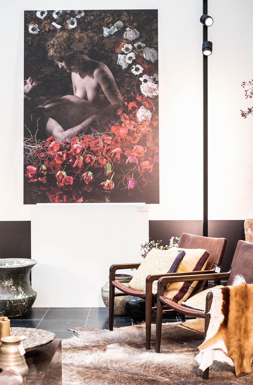 Enkele mooie stoelen staan in een witte ruimte met een schilderij met bloemen aan de muur.