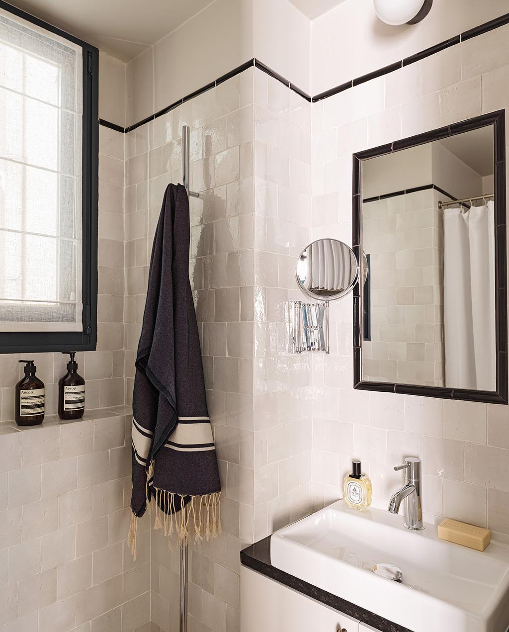 vtwonen special tiny houses   witte tegels in de badkamer met aan de bovenkant een zwarte lijn, en een zwarte doek I weg met die witte muren