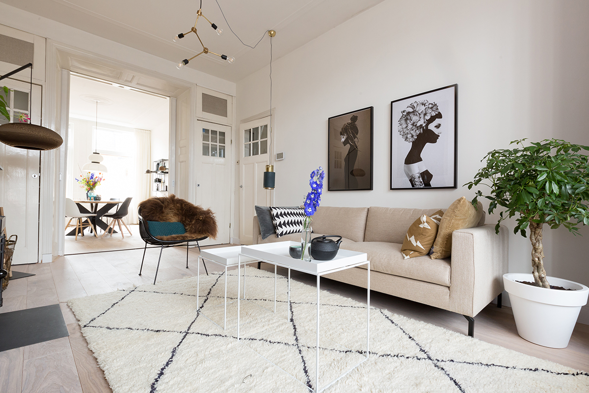 Woontrend voorjaar fine lines and simplicity woonkamer zwart wit tapijt beige bank schilderijen