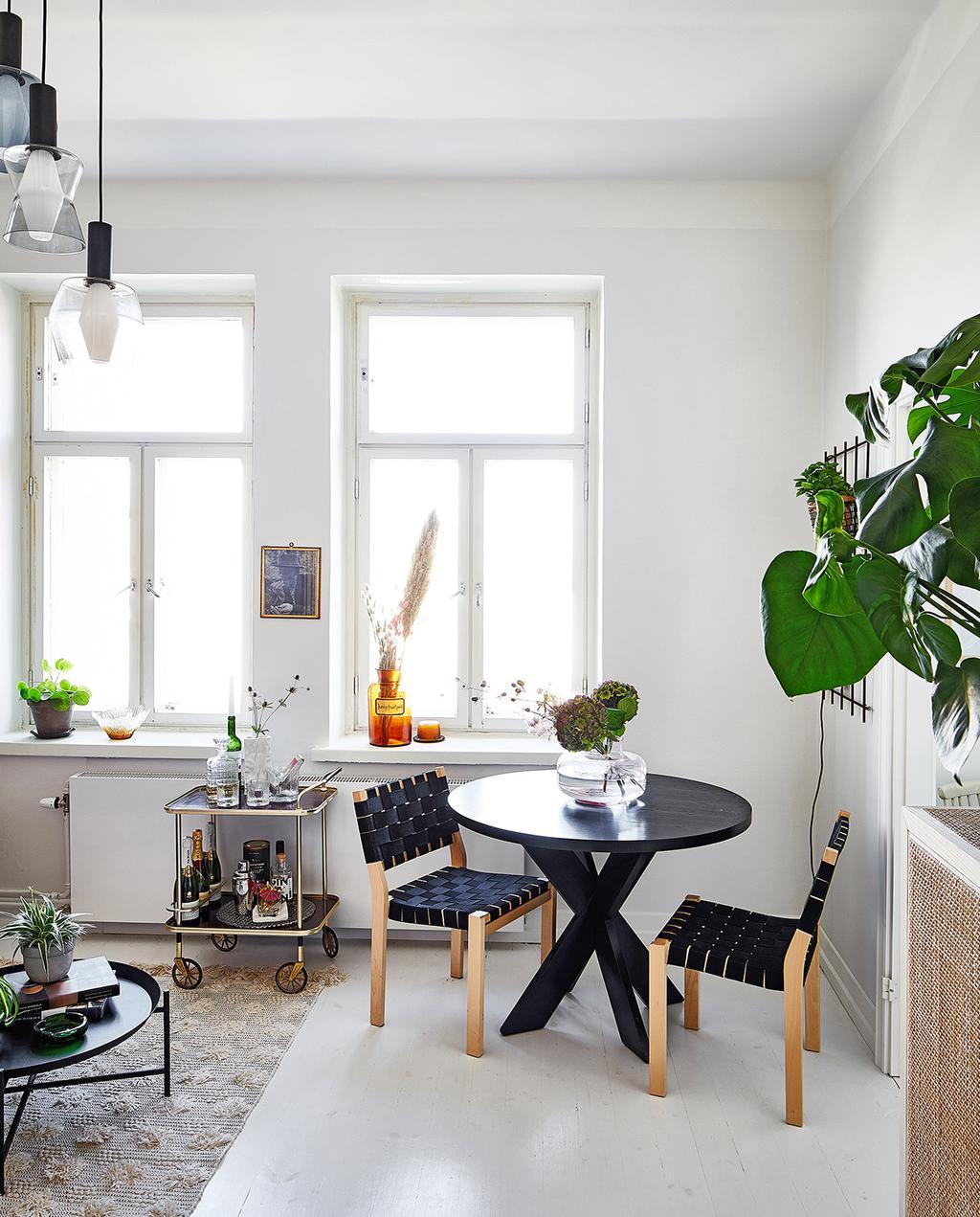 vtwonen special tiny houses | ronde zwarte eettafel met twee stoelen en een barwagen