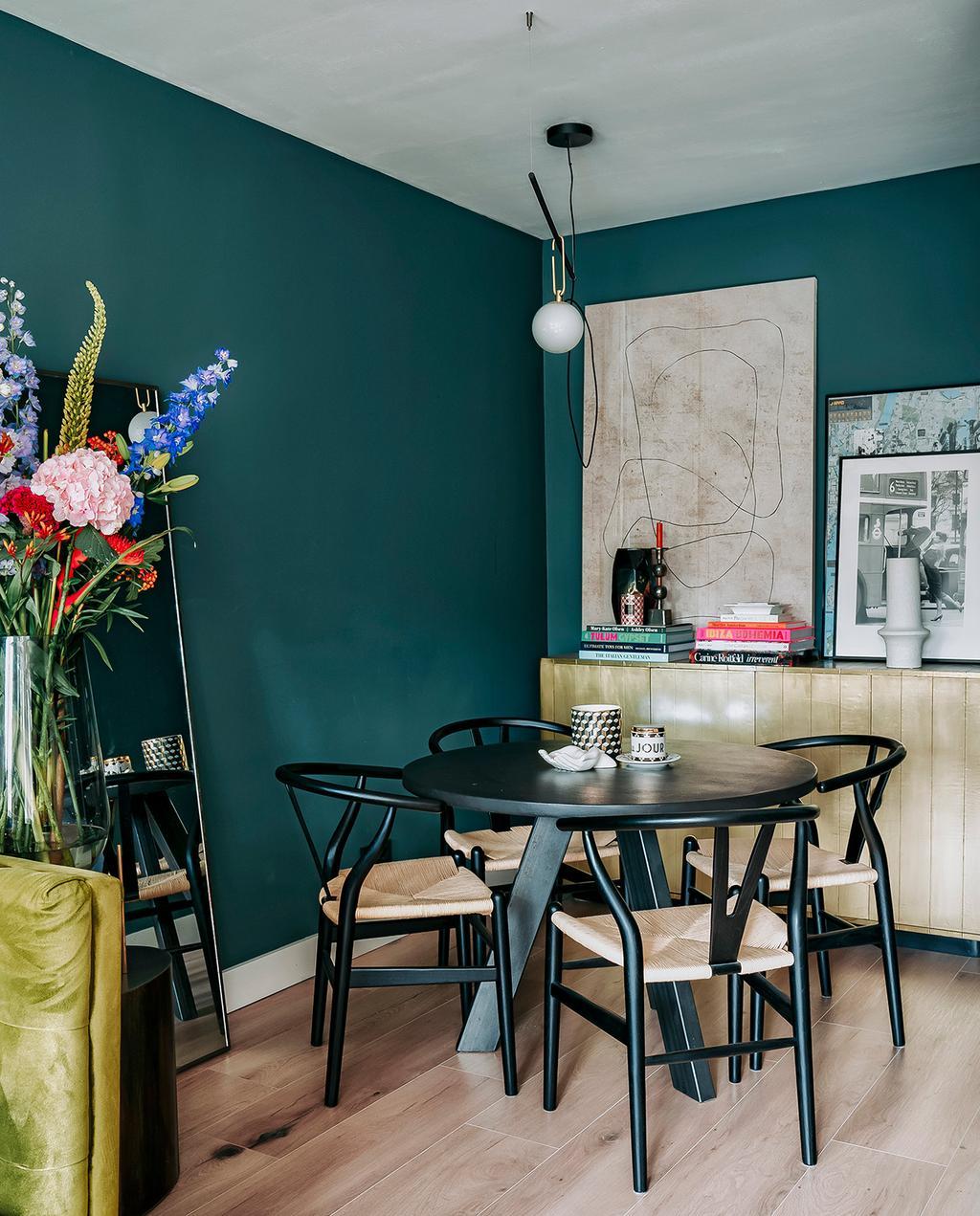 vtwonen 06-2021 | groene muur met zwarte ronde tafel en eetkamerstoelen
