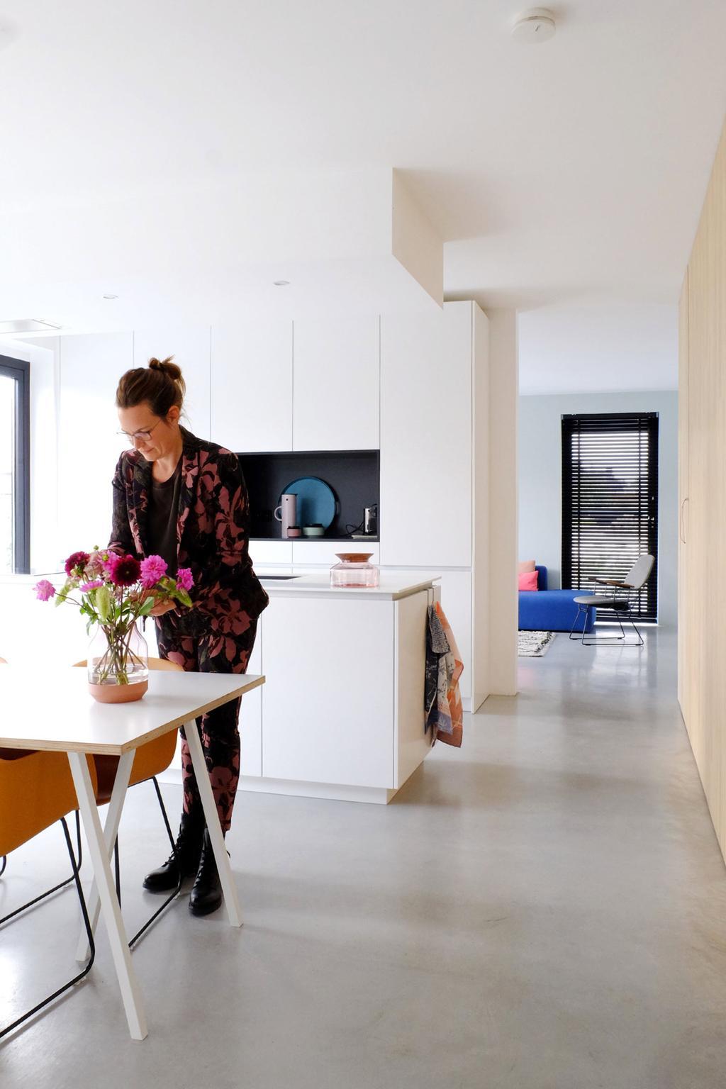 Witte keuken van PRCHTG met eettafel en beton vloer.