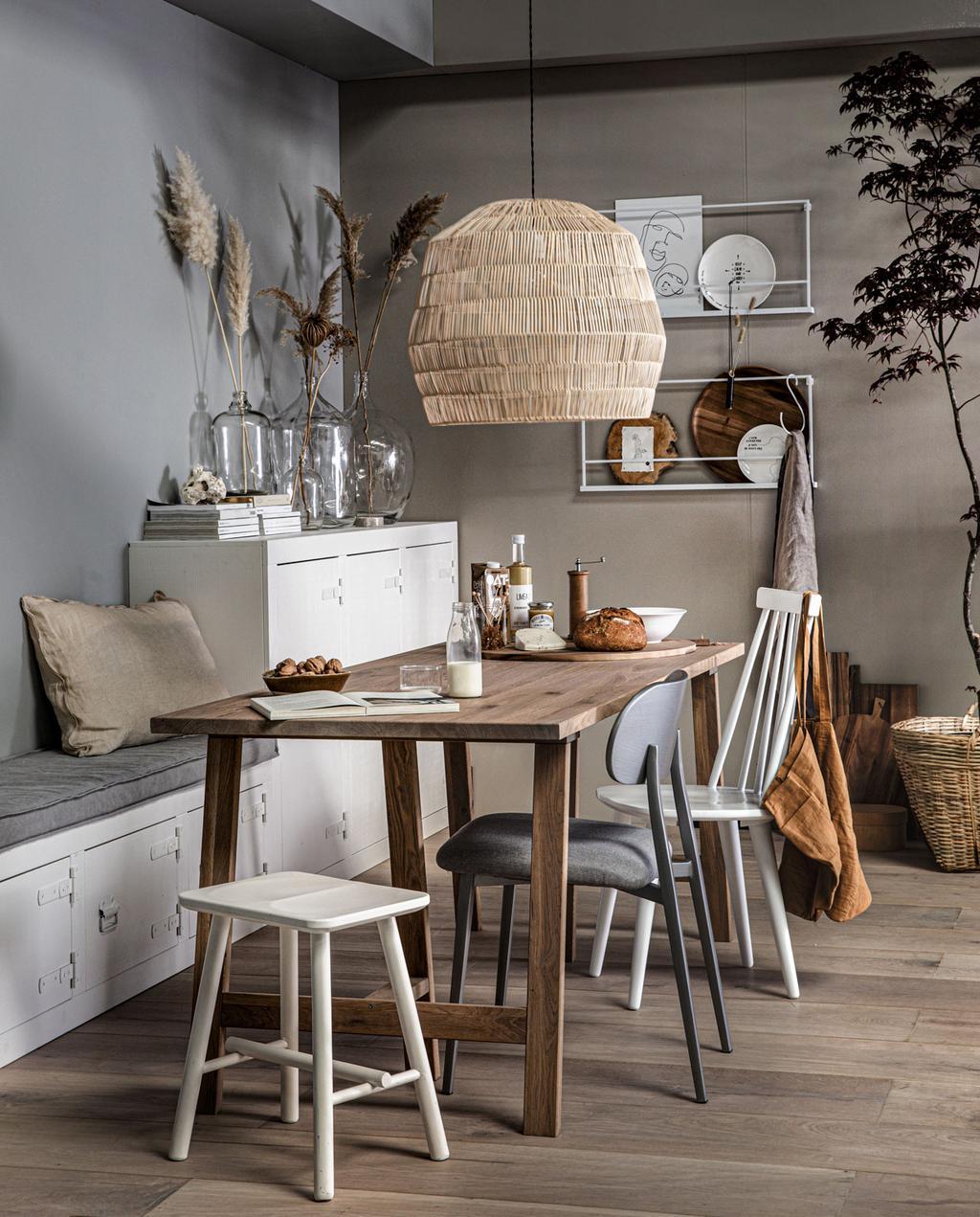 eetkamer bruine muur met tafel en verschillende stoelen en krukjes