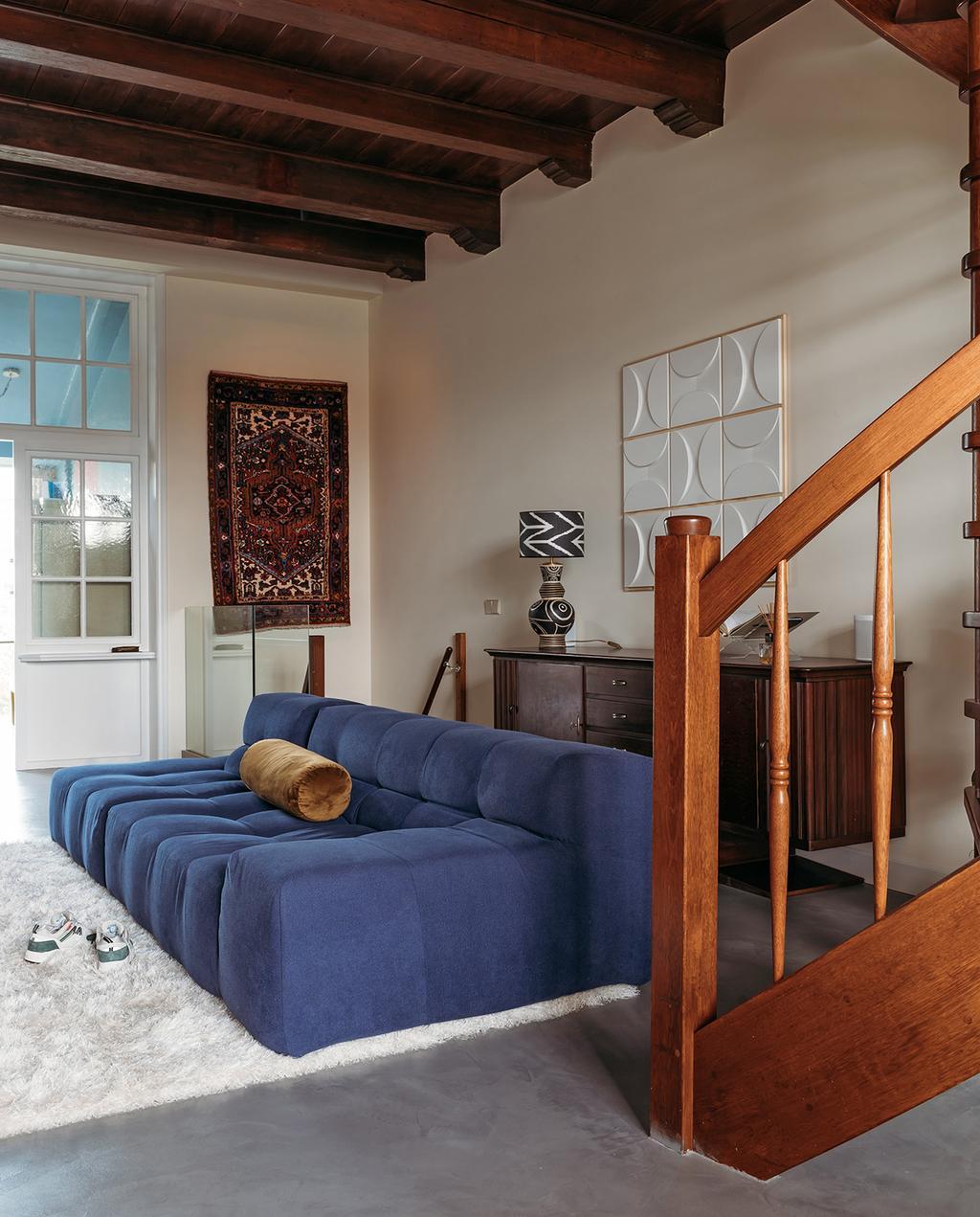 vtwonen 03-2021 | woonkamer met blauwe bank en Perzisch tapijt aan de wand
