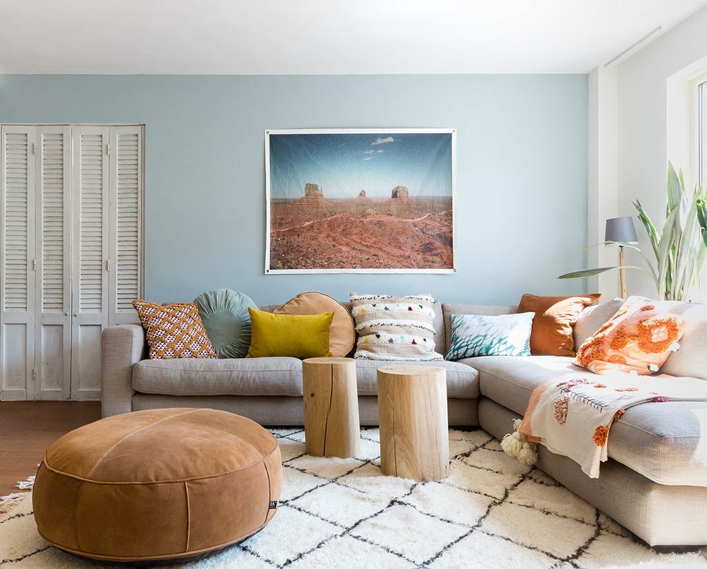 Grote grijze hoekbank in de woonkamer met blauwe wand, canvasdoek en grote bruine poef