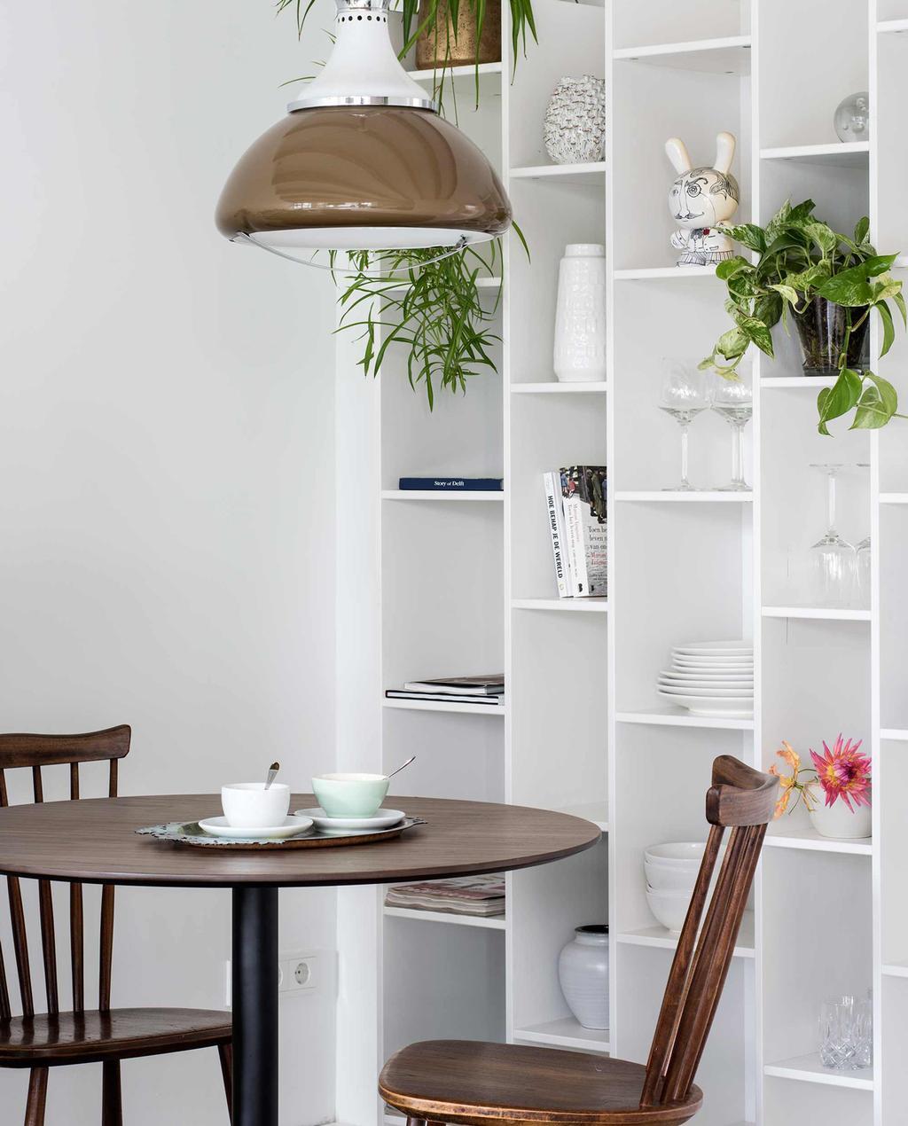 witte boekenkast met planten en servies naast donkerbruine vintage houten tafel