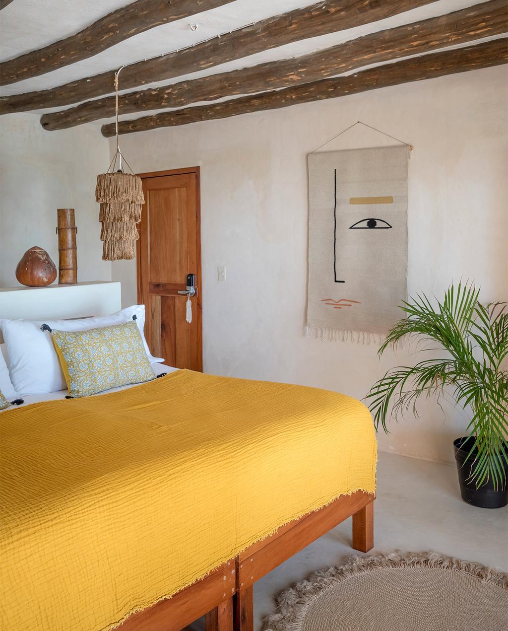 vtwonen special zomerhuizen 07-2021 | geel dekbedovertrek sprei in de slaapkamer met Mexicaanse stijl