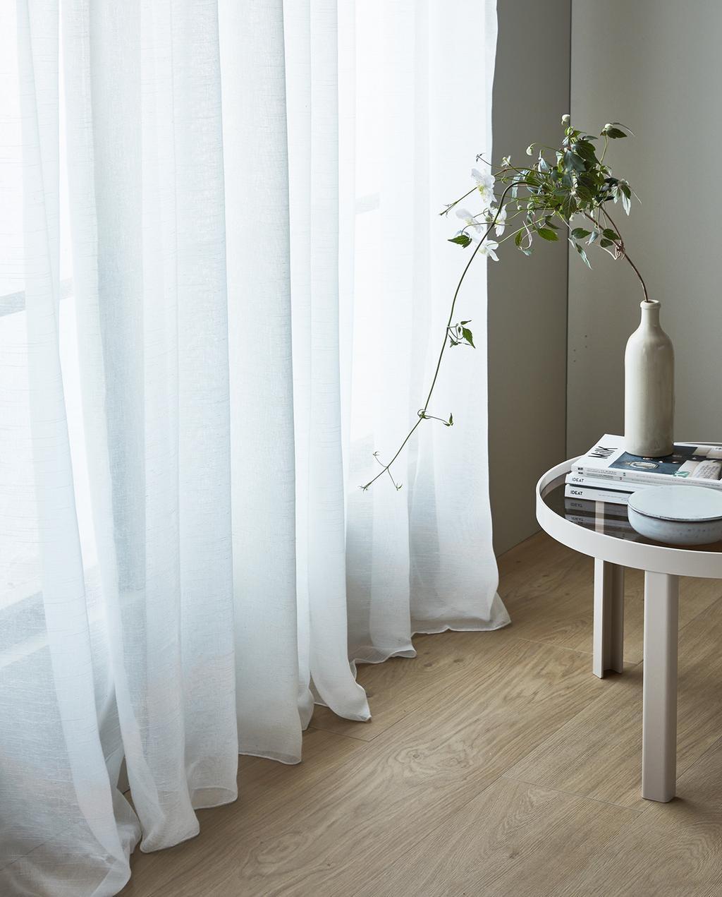 vtwonen 07-2021 | witte gordijnen met een vaas op de bijzettafel en vtwonen vloer I nieuwe gordijnen