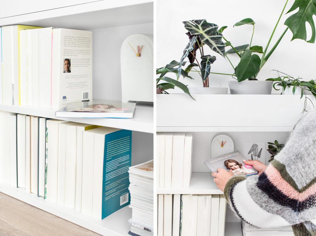 Witte boekenkast met boeken en planten