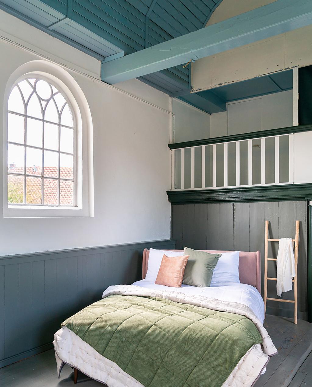 heilige nachten en made.com | overnachten in een opgeknapte kerk | roze bed met groene sprei bij groot raam