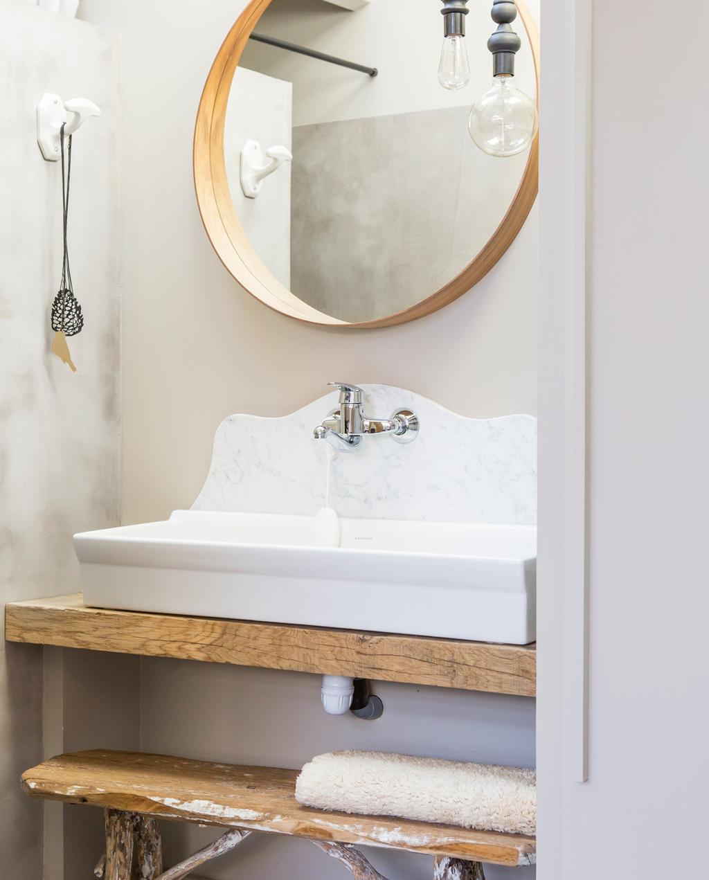 vtwonen binnenkijken special 07-2021 | binnenkijken in een vissershuis | kleine badkamer met grijze tadelakt tegen de muren, een ronde spiegel en een antieke wasbak op een oud houten wastafel