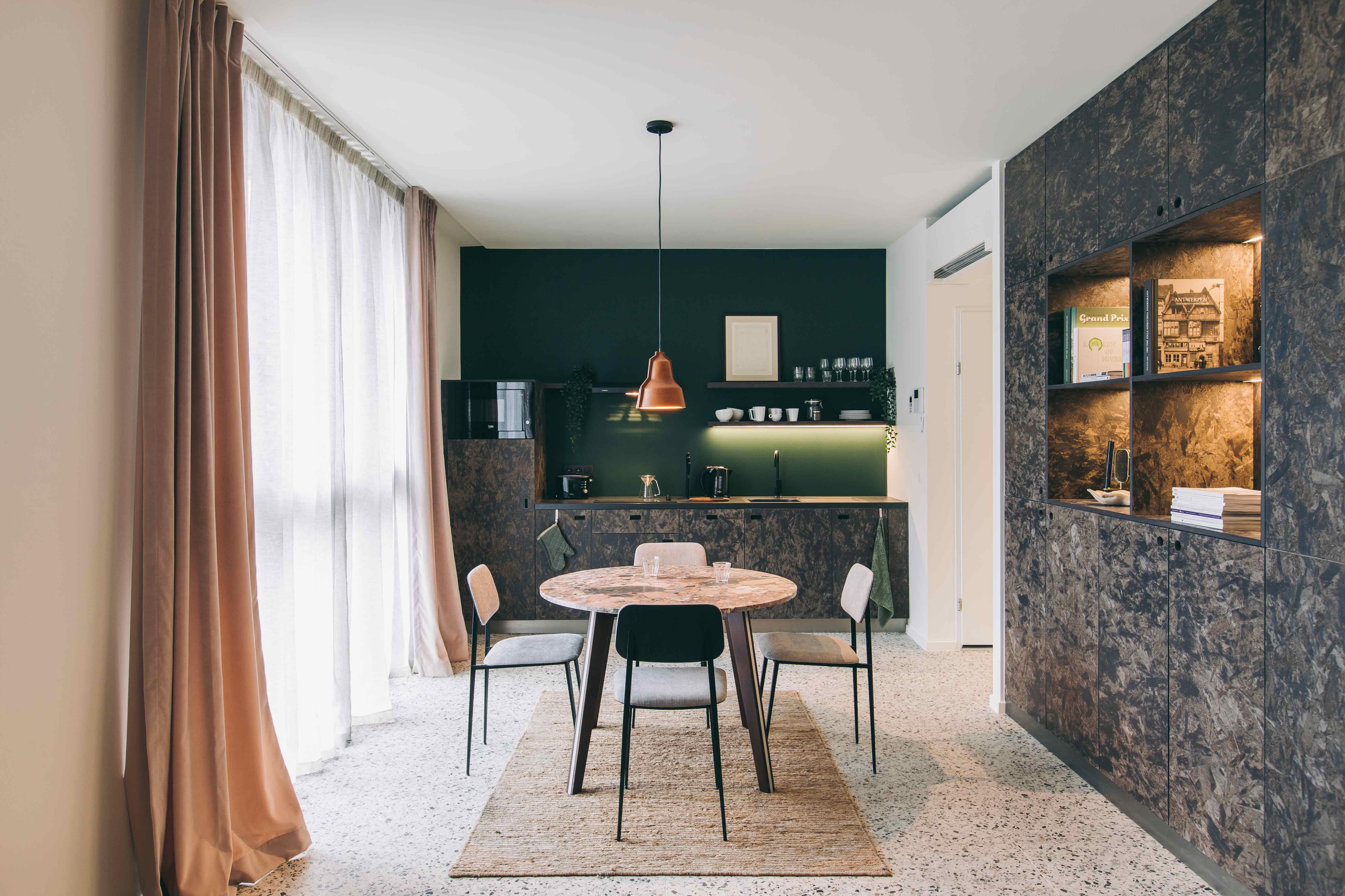 YUST Antwerpen, eetkamer met veel lichtinval, compacte keuken met groene en accenten