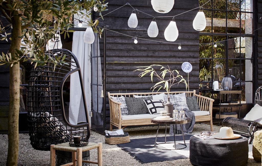 Maak je balkon en terras zomerklaar. zwarte tuin met bamboe bankje en zwarte hangstoel | vtwonen