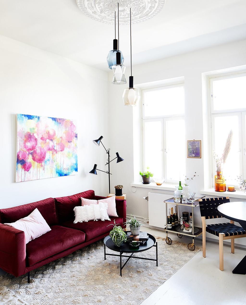 vtwonen special tiny houses | woonkamer van de woning in Helsinki met een rode bank en groot vloerkleed
