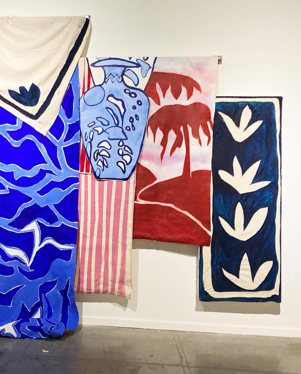 vtwonen 02-2021 | verschillende kunstwerken aan de wand, rechts met bloemen, midden met palmbomen en links met blauwe lijnen
