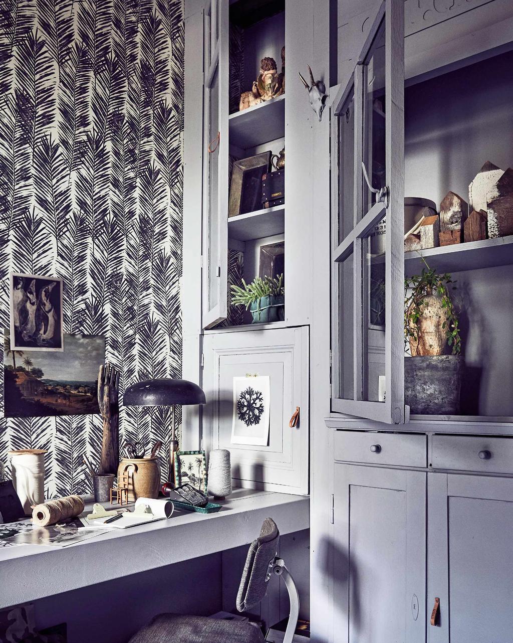 Warm interieur met grijze werkplek met botanisch behang en vitrinekast om in op te bergen