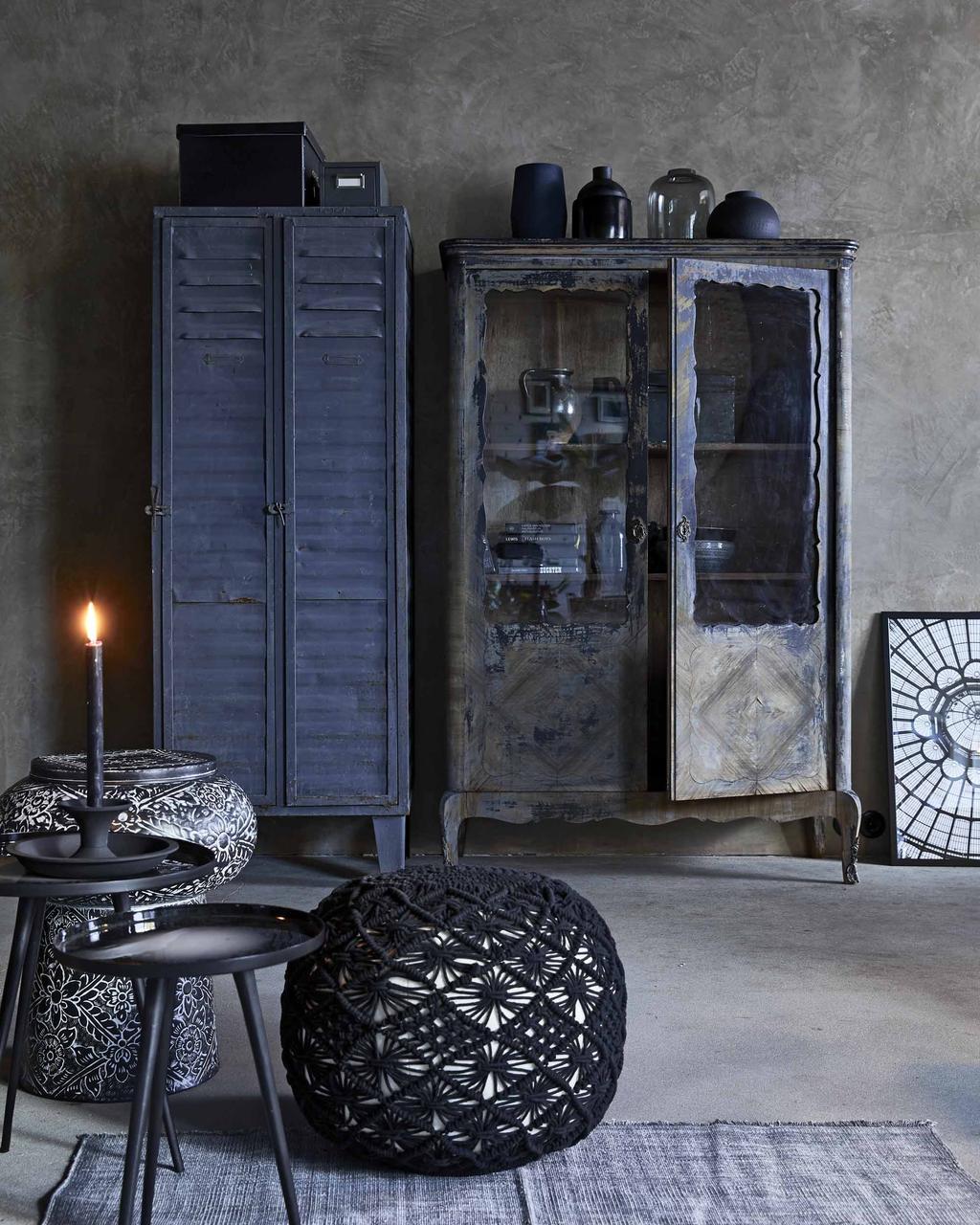 Vintage zwarte kasten met zwart gehaakte poef en zwarte tafel met kandelaar