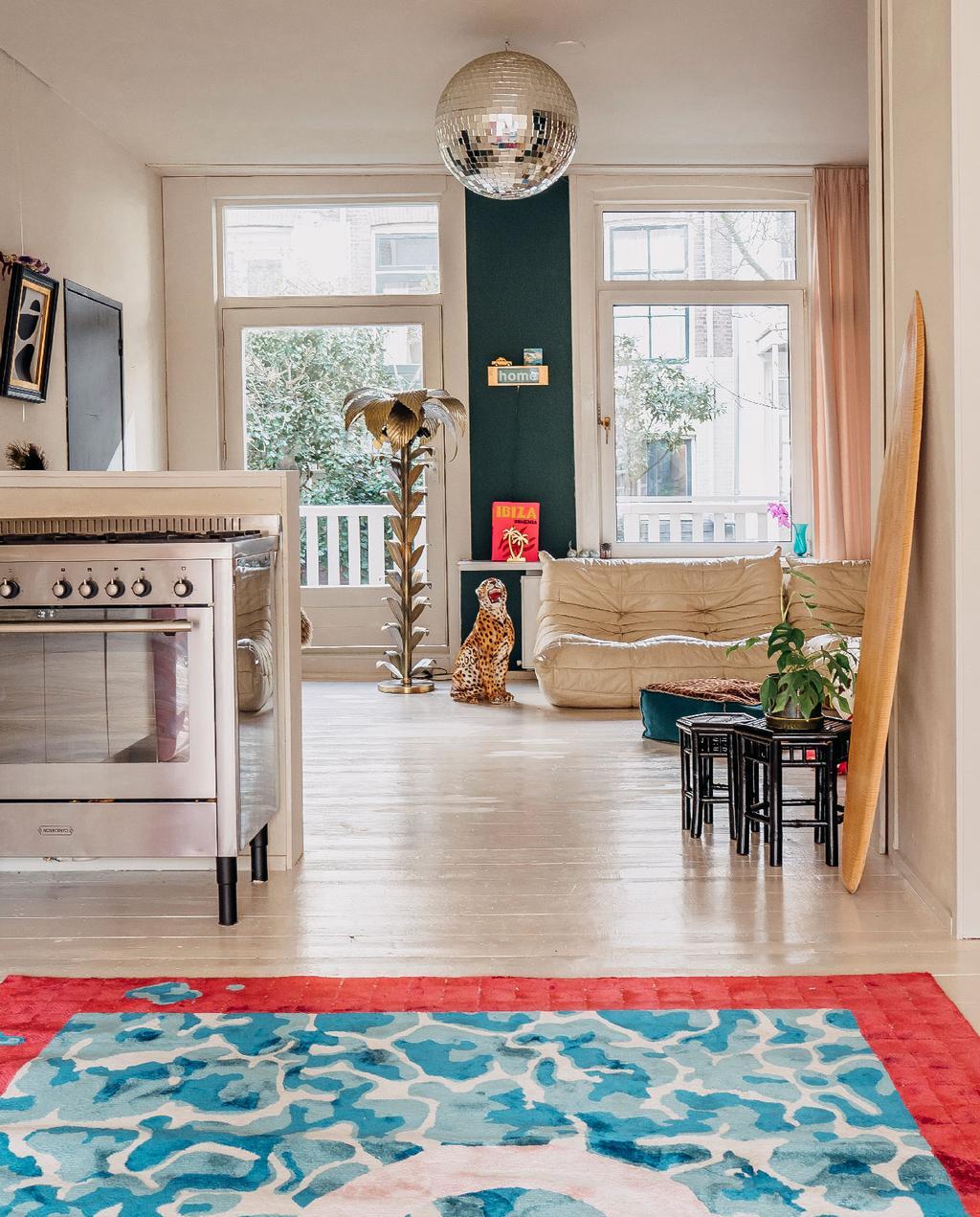 vtwonen 11-2020 | binnenkijken amsterdam open leefkeuken vloerkleed met blauw dessin, discobal aan het plafond, donkergroene muur en togo bank wit leer