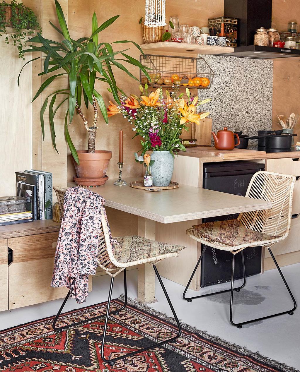 vtwonen binnenkijken special tiny houses | houten eettafel en stoelen in de keuken met zwarte koelkast en kandelaar