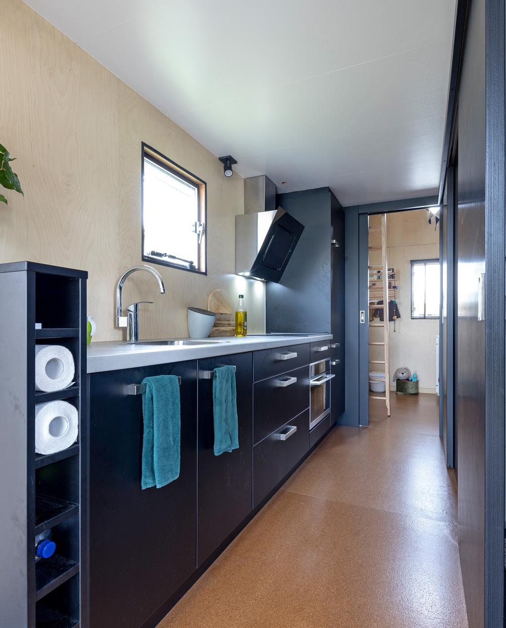 vtwonen special tiny houses | zwarte keuken zonder bovenkastjes met een zilvere kraan