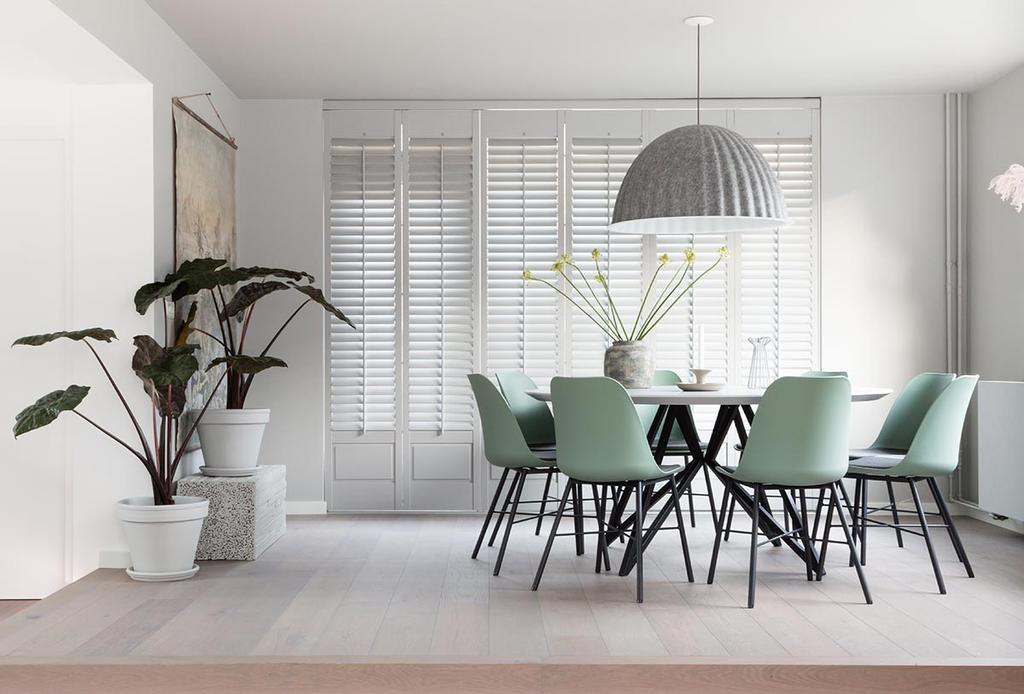 Weer verliefd op je huis: eethoek met groene eetkamerstoelen en hanglamp van beton