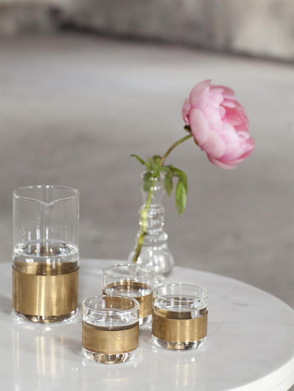 nachtkastje met karaf en bloem. Gouden randje aan glas.