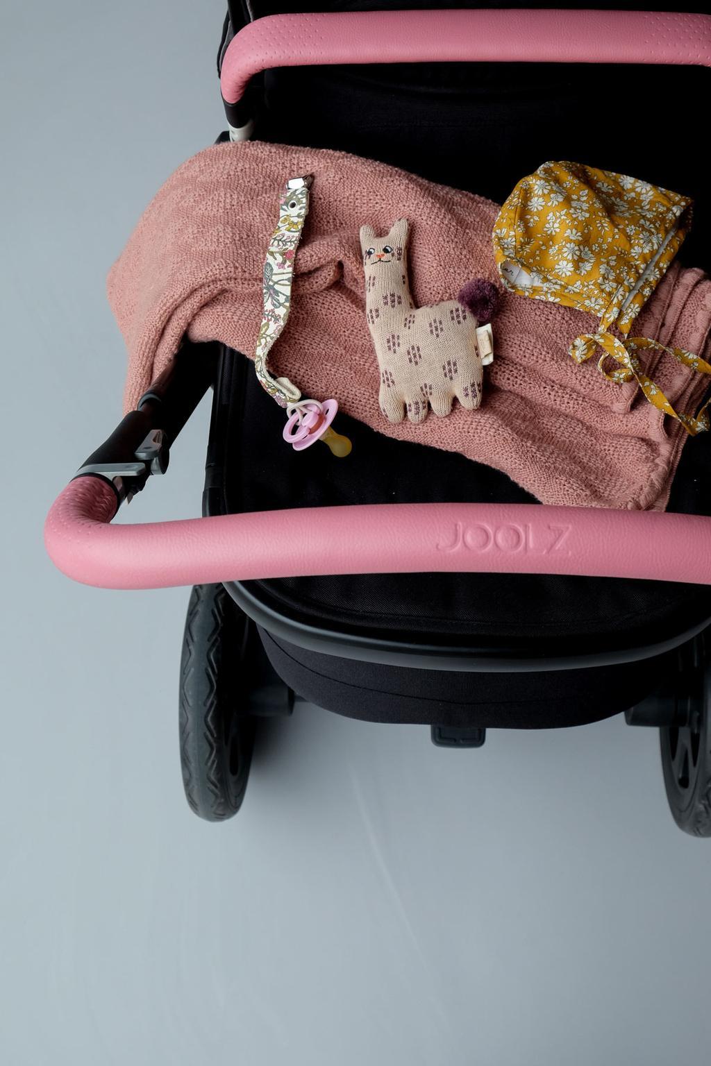 Kinderwagen van het merk Jools met roze accenten.