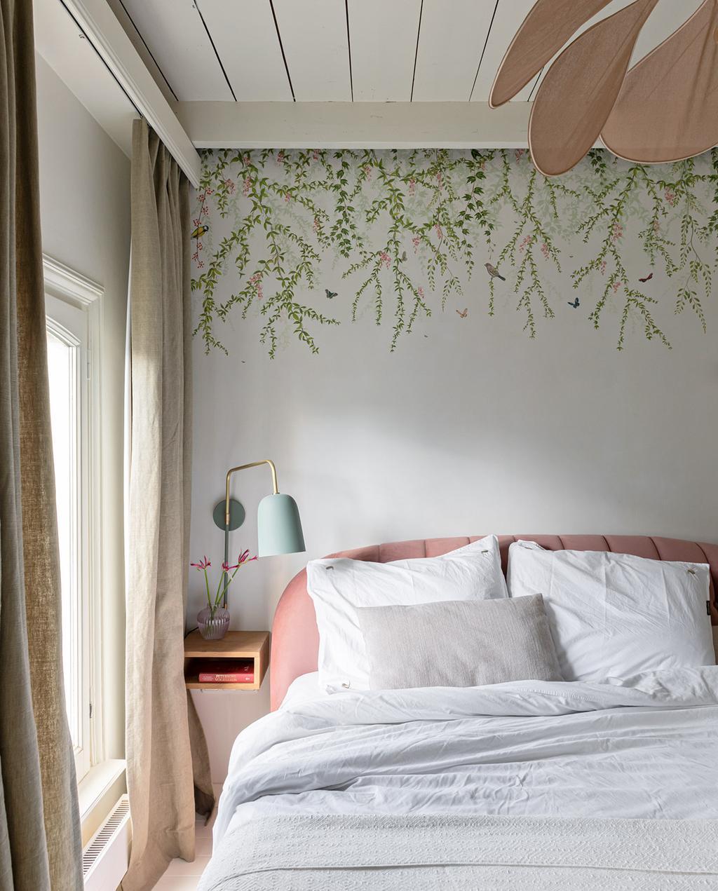 vtwonen special tiny houses | slaapkamer in Utrecht met behang van bloemen en opgemaakt roze bed met blauwe lamp