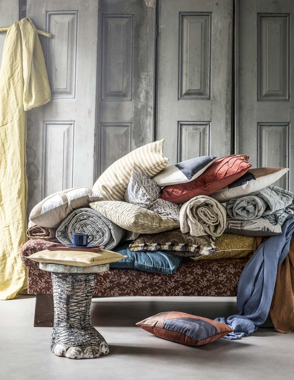 In de styling wonen met lef breng je natuurlijke kleuren in huis met kussens, plaids en kleden in herfst tinten.