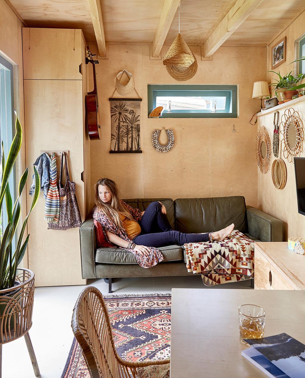 vtwonen binnenkijken special tiny houses | carmen op de bank met spiegels aan de muur en een vloerkleed met motief