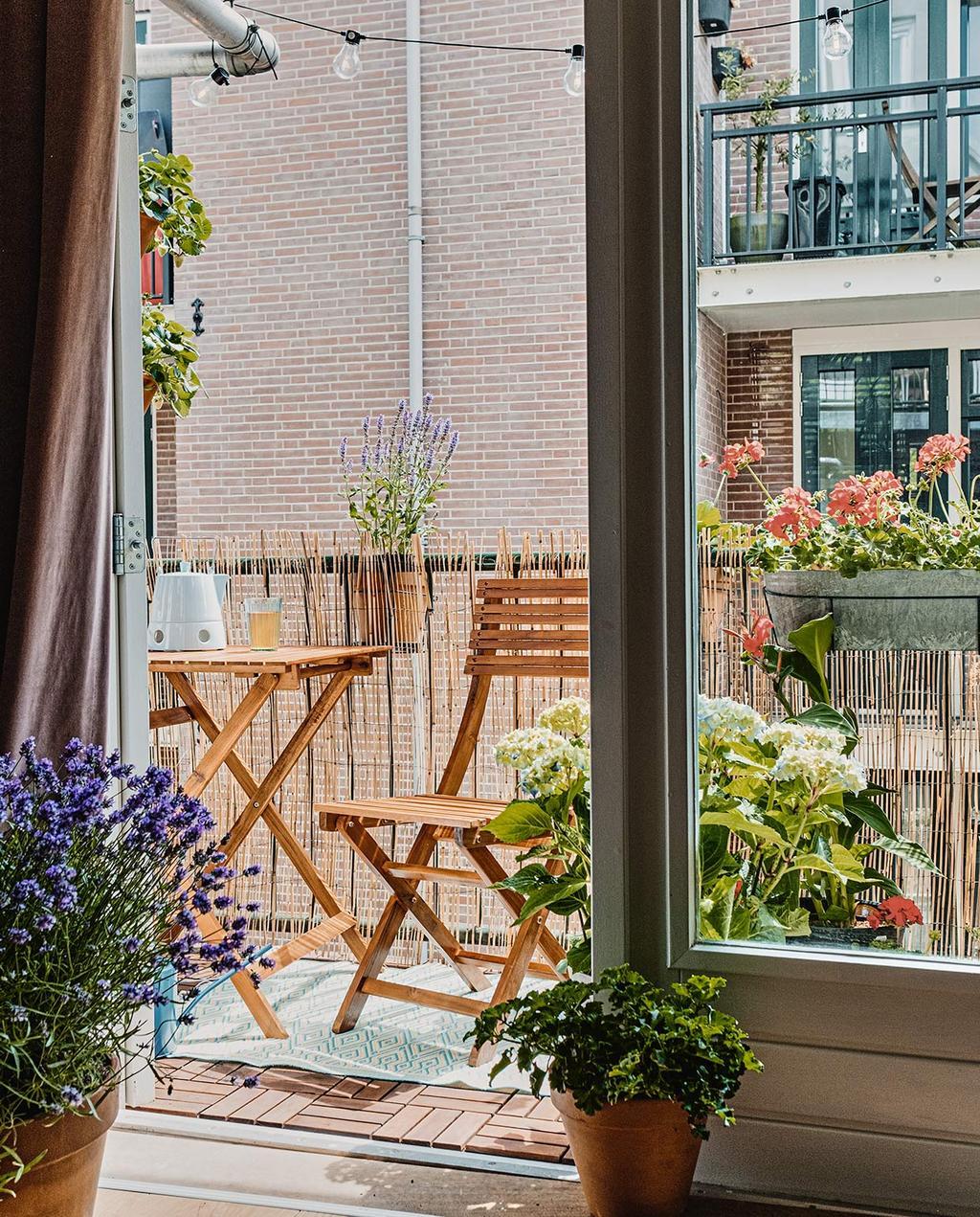 vtwonen 02-2021 | balkon met tuintafel en stoel en veel planten