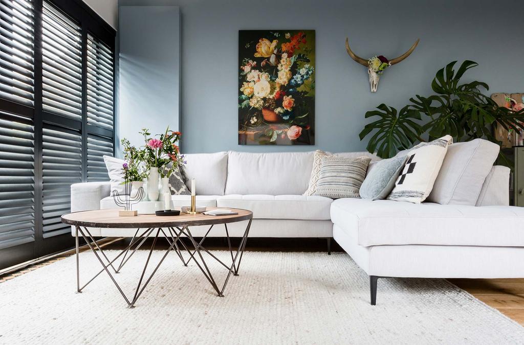 grijze hoekbank blauwe wand bloemen schilderij