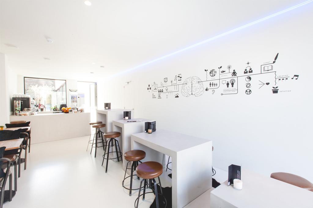 Het witte en serene interieur van de koffiebar van SO in Leuven